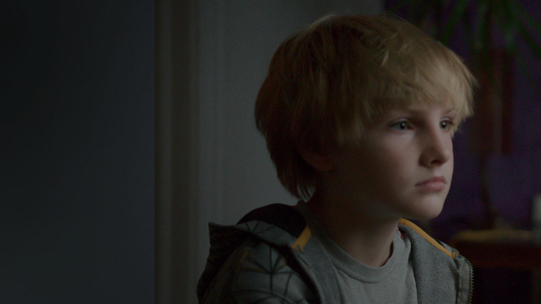 Un jeune garçon nommé Beckett assis et regardant vers la droite.
